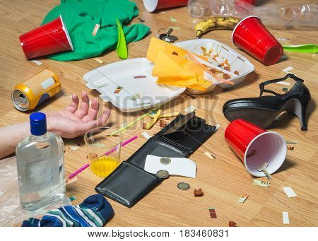 Man passed out on the floor after wild partying, hand visible. Terrible hangover and mess in the apartment. Trash, food leftovers, clothes, high heels and bottles everywhere. Regret and remorse. poster