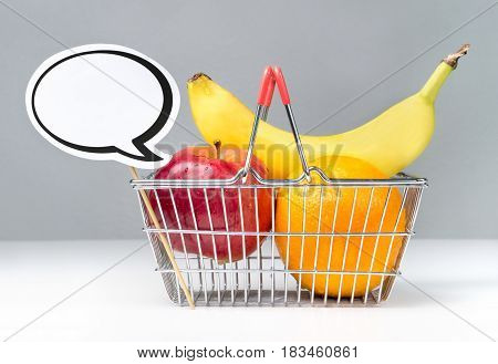 Speech bubble with shopping basket of fruits. Apple, orange and banana in basket with speech balloon. Fun vegan and vegetarian healthy food concept.