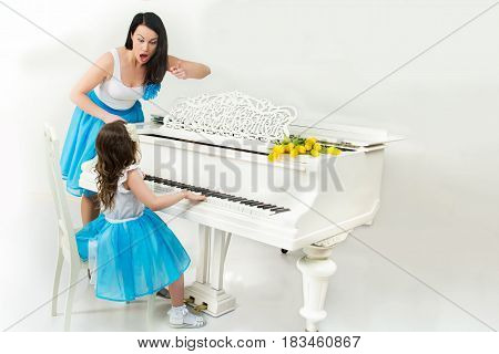 Strict music teacher scolds the student who sits at a white piano in a music school.