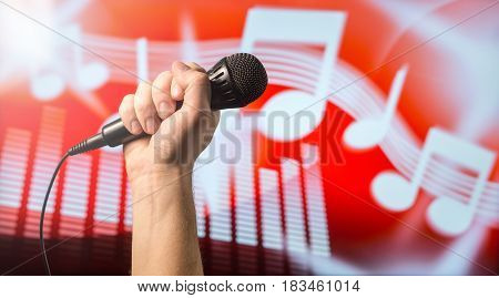 Singing, karaoke or vocal training concept. Microphone in hand in front of an abstract music themed note and equalizer background. Song contest and live performance vibe with copy space for text.