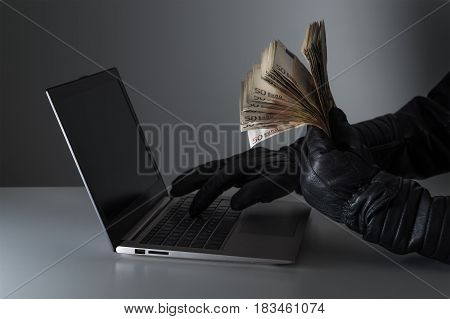 Criminal holding a lot of money and using laptop with black leather gloves. Hacker steal funds with computer. Internet fraud and cyber security concept.
