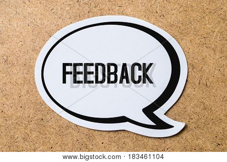 Feedback text in a speech bubble cut from paper or cardboard. High contrast picture with a light brown wooden cork board background. Useful icon styled design to website or social media for business.