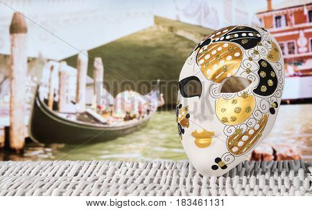 Mask from Venice with a gondola moored by Rialto Bridge. Golden and decorative souvenir and a traditional Venetian boat in the canal in the blurred background. Summer holiday and travel concept.