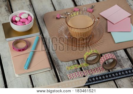 Cup of tea, sticky notes, paper pins, clips, printed sellotape, ruler and pen on wooden plank