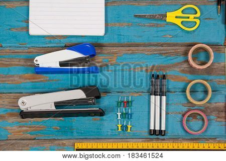 Notepad, stapler, pins, sellotapes, ruler and pens on wooden plank