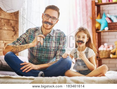 Happy father's day! Dad and his child daughter are playing and having fun together. Beautiful funny girl and daddy have mustaches on sticks. Family holidays and togetherness.