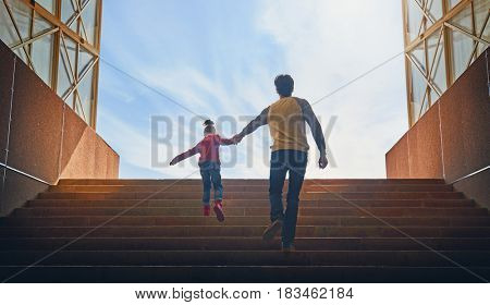 Father and child climb upstairs. Cute girl pulls her dad hand.