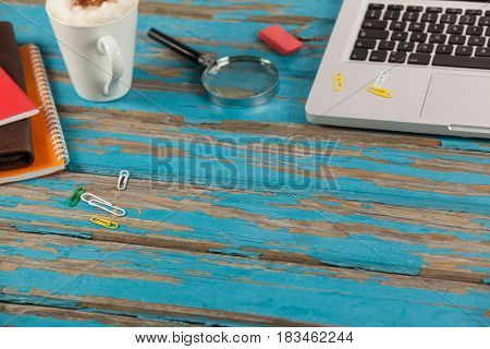 Laptop, coffee mug, diaries, magnifying glass and paper pins on wooden plank