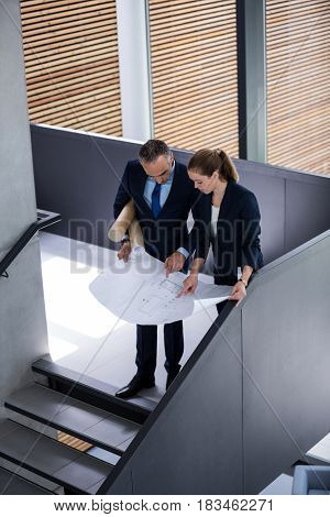 Business colleagues discussing on blueprint while standing on staircase in office building