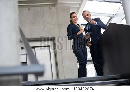Business colleagues standing on a staircase and talking to each other at office building