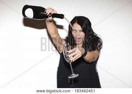 Cheerful young woman pouring champagne to the glass. Horizontal indoors shot.