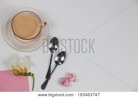 Cup of tea, spoons, blank page, paper balls and flower on white background