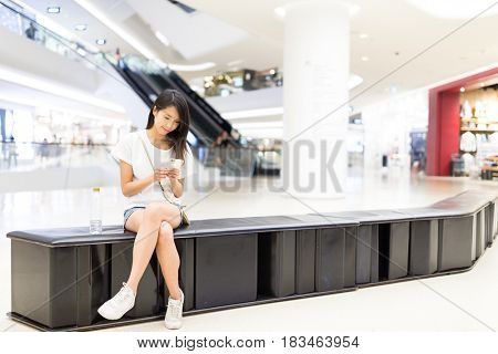 Woman sending sms on cellphone in shopping mall
