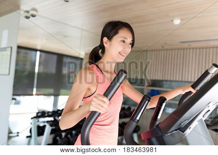 Sport Woman training on Elliptical machine in gym