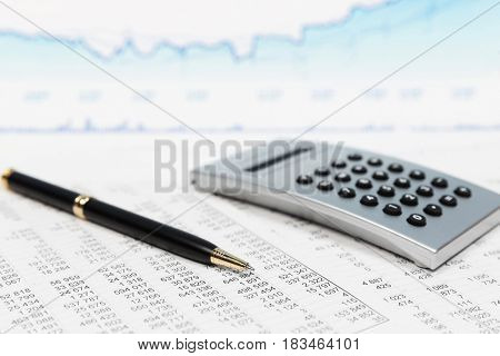Financial accounting stock market graphs and charts analysis. Pen and calculator on reports