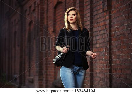 Young blond business woman with handbag walking in city street. Stylish fashion model in black jacket and blue jeans outdoor