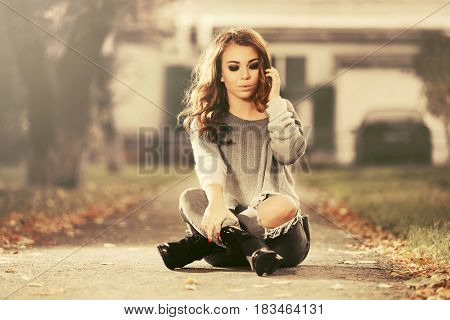 Sad young woman in ripped jeans sitting on sidewalk. Stylish fashion model with long curly hairs outdoor