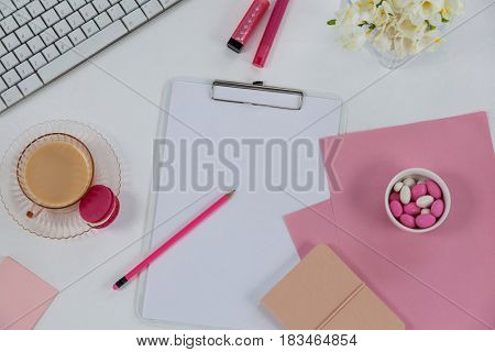 Cup of tea with macaroon, keyboard, diary, pebbles, flowers, clipboard, pencil and sticky note on white background