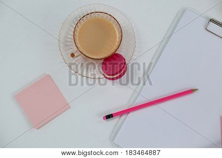 Cup of tea with macaroon, clipboard, pencil and sticky note on white background