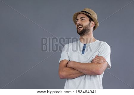 Happy man in white t-shirt and fedora hat against grey background