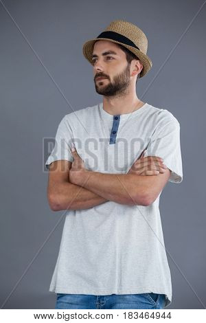 Man in white t-shirt and fedora hat against grey background