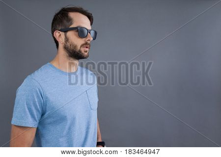 Man in blue t-shirt and sunglasses against grey background