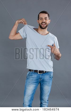 Portrait of a cheerful man posing in grey t-shirt against grey background
