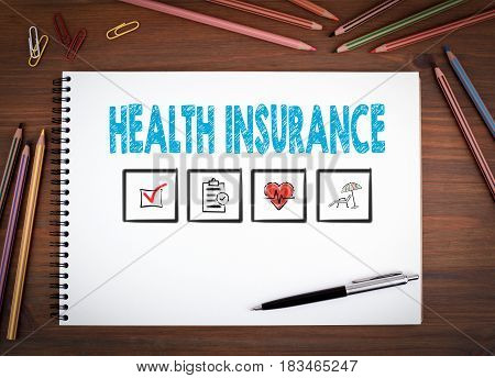 Health Insurance. Notebooks, pen and colored pencils on a wooden table.