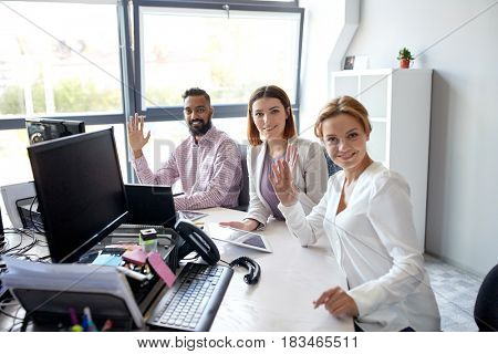 corporate, technology and people concept - business team with tablet pc and computers waving hands at office