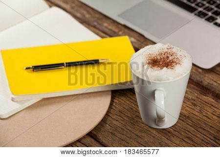 Coffee mug, diary, pen and laptop on wooden background