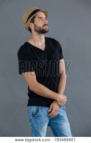 Man in black t-shirt and fedora hat standing against grey background