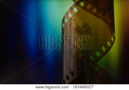 camera roll with negatives on rainbow background, film industry