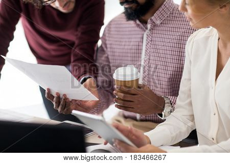 business, startup and people concept - international creative team with papers, tablet pc computer and coffee cup in office