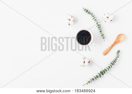 Workspace with cup of coffee cotton flowers eucalyptus branches wooden spoon. Flat lay top view