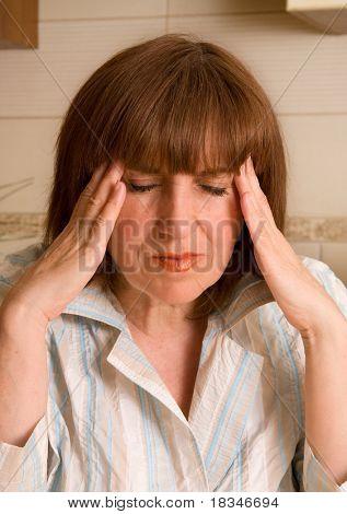 Headache. The woman keeps for a head