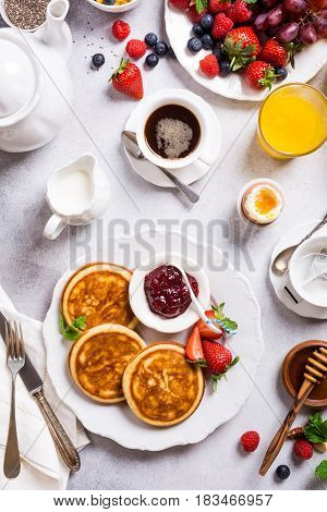 Healthy breakfast with fresh hot pancakes with berry jam on light gray background, top view.