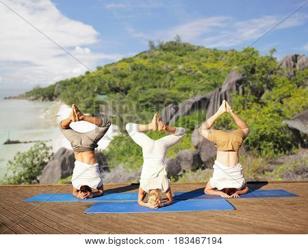 fitness, sport, yoga and healthy lifestyle concept - people making headstand pose on mat over tropical beach background