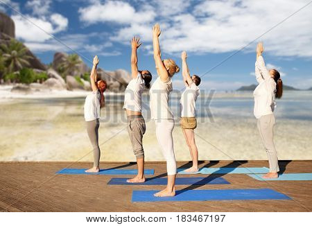 fitness, sport, yoga and healthy lifestyle concept - group of people making upward salute pose over tropical beach background