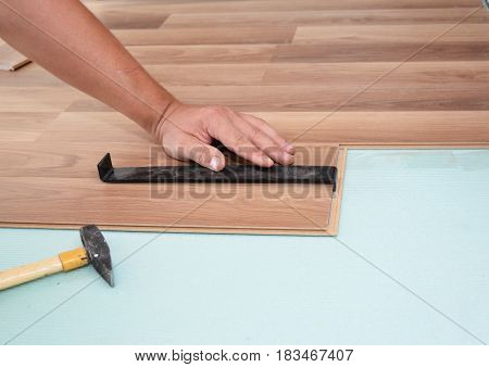 Installing laminate flooring. Man Installing New Laminate Wood Flooring. Worker Installing wooden laminate flooring with hammer. Handyman laying down laminate flooring boards while renovating a house.