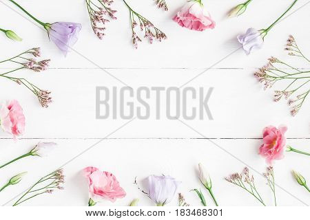 Flowers composition. Frame made of various flowers on white wooden background. Flat lay top view