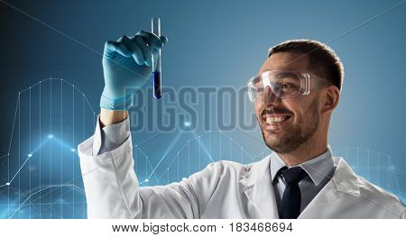 science, chemistry, medical research and people concept - young smiling scientist in safety glasses with test tube and diagram projection over blue background