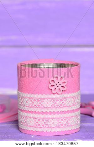 Decorative can on wooden background. Old tin can decorated with pink felt, white lace and flower button. Easy and cheap recycled tin can crafts and projects for home. Closeup. Vertical photo