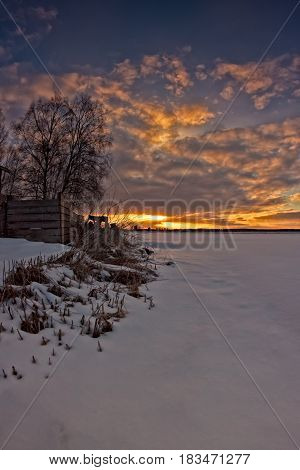 The sun sets behind the horizon in the rural Finland. It's spring but there is still quite a lot of snow on the fields.