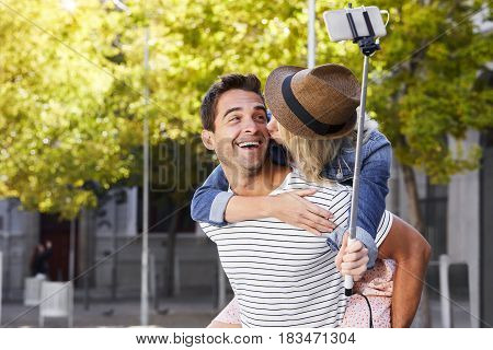 Kissing selfie couple in city - smiling