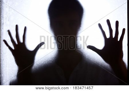 Man Leaning Against Glass Wall