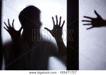 Man Standing Behind Glass Door
