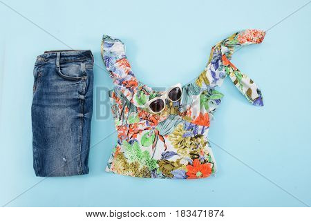 Fashion. Summer woman accessories-Summer floral clothes with sunglasses,jean on blue background