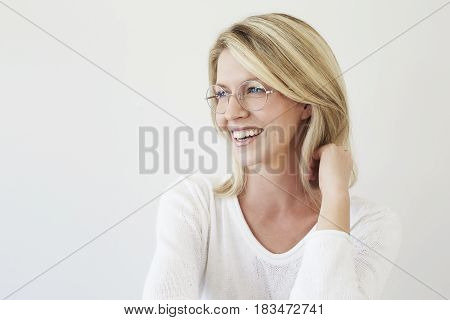 Beautiful blond woman in glasses smiling studio Shot