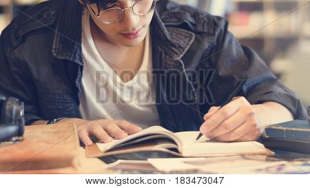 Asian student boy studying in school library