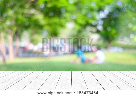 Empty white table perspective wood over blur park with people background for product display montage background